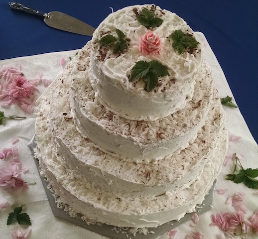 A four-tier wedding cake, looks like chocolate and coconut flavour.