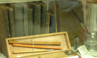 A number of old books and some writing instruments.