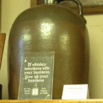 Brown jug with sign: If whiskey interferes with your business, give up your business.