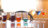 Several glasses of liquids in various colours.
