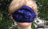 "Boy wearing mask over eyes that reads ""NO MASKS"""